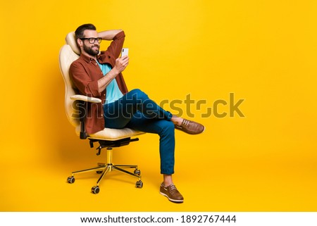 Full length body photo of smiling freelancer keeping smartphone social media sitting in chair pause isolated vibrant yellow color background Royalty-Free Stock Photo #1892767444