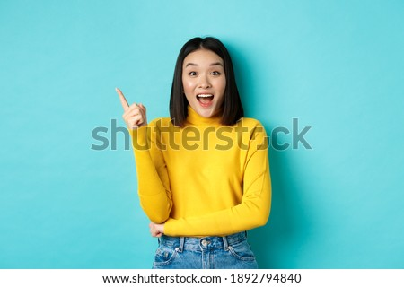 Shopping concept. Attractive korean woman smiling amazed, pointing finger left, showing good deal banner, standing against blue background