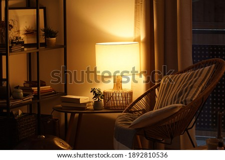 View of a cozy reader's corner with a table lamp spending warm light Royalty-Free Stock Photo #1892810536