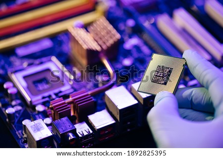 Laboratory technician holds a powerful processor in his hands. CPU computer processor. CPU socket of the computer's motherboard. Concept of computer, motherboard, hardware and technology Royalty-Free Stock Photo #1892825395
