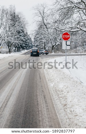 Car collision at the crossroads in winter - snow and ice on the road - did not give way and drove to the STOP sign