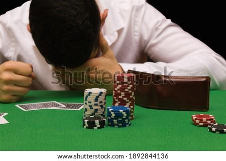 Devastated gambler man losing a lot of money playing poker in casino, gambling addiction. Divorce, loss, ruin, debt, ludopata concept Royalty-Free Stock Photo #1892844136