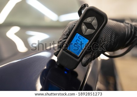 Detailing worker checks the condition of the paintwork with electronic thickness gauge. Car polishing concept Royalty-Free Stock Photo #1892851273