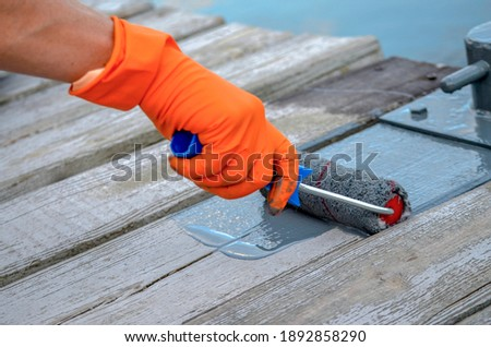 Fresh glossy gray paint on wooden boards applied with a paint roller Royalty-Free Stock Photo #1892858290