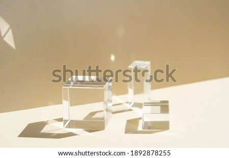 Minimal modern product glass display on textured background in neutral earth tones with shadows Royalty-Free Stock Photo #1892878255
