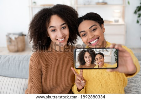Selfie friends in free time, stay at home together. Happy millennial african american sisters take photo, show peace sign and hold smartphone with picture, sits on sofa in living room interior