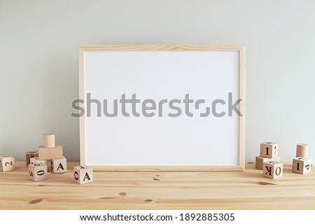 Neutral nursery horizontal frame mockup, empty wooden frame in baby room to showcase artwork, print, photo, painting.         Royalty-Free Stock Photo #1892885305