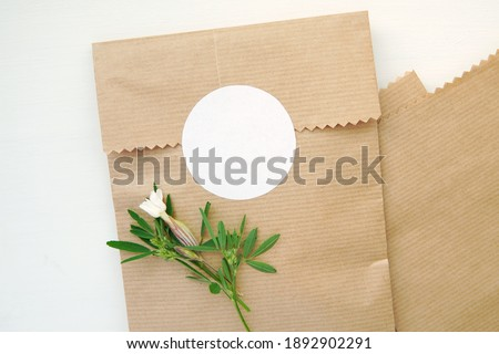 Round blank sticker mockup, circle tag mock up on kraft paper gift bag, adhesive round product label. Royalty-Free Stock Photo #1892902291