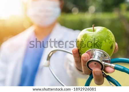 World health day, an apple a day keeps the doctor away concept for health benefit by eating high nutritious clean food and healthy nutritional diet with doctor handling green apple giving to patient Royalty-Free Stock Photo #1892926081