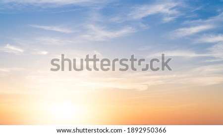 Sunset sky in the morning with colorful orange sunrise on blue white clouds Royalty-Free Stock Photo #1892950366