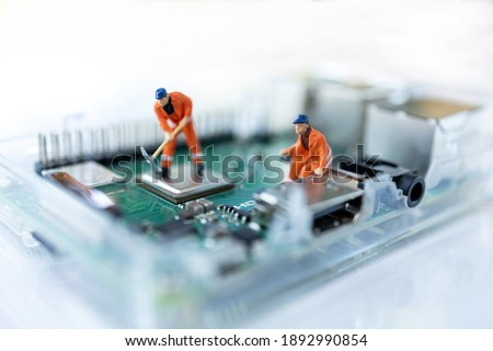 Miniature people searching or checking for bugs and issue on microchip, mainboard of computer. Vulnerability search and security system concept. Royalty-Free Stock Photo #1892990854