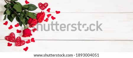 Bouquet of red roses and hearts on white background. Valentine's day, banner format. Place for text.