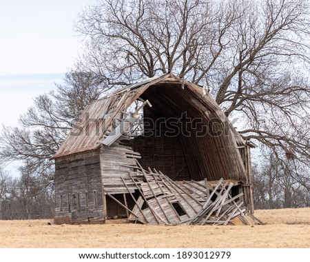 Old abandoned barn that has started to collapse  Royalty-Free Stock Photo #1893012979
