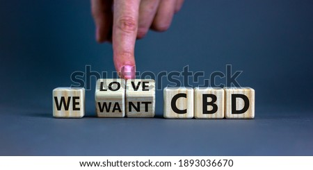 We love CBD, cannabidiol symbol. Hand turns cubes and changes words 'We want CBD' to 'We love CBD'. Beautiful grey background, copy space. Medical and we love CBD cannabidiol concept. Royalty-Free Stock Photo #1893036670