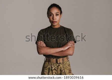Confident african american soldier woman posing with arms crossed isolated over grey wall Royalty-Free Stock Photo #1893039616