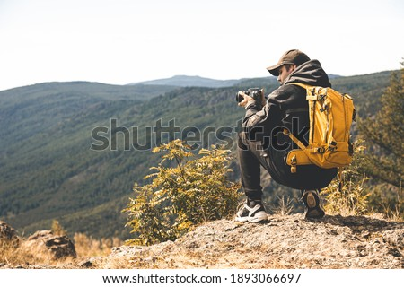 A man with a yellow backpack goes hiking in the mountains and takes pictures of nature