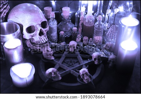 Necromancer's dark ritual with pentagram, candles and skulls