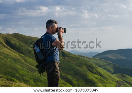 A side shot of a traveling photographer taking pictures of scenic nature, picturesque mountains in the backgrou