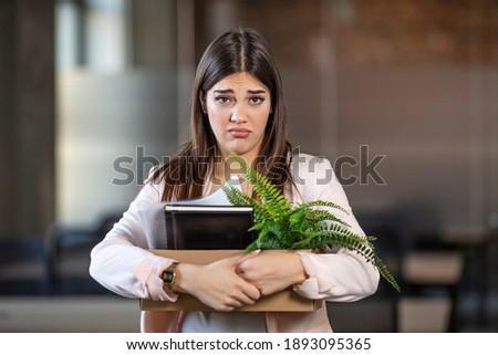 Sad woman leaving the office and carrying her belongings after getting fired from work due to COVID-19 pandemic. Unemployed businesswoman lost her business. Anxious concept Royalty-Free Stock Photo #1893095365