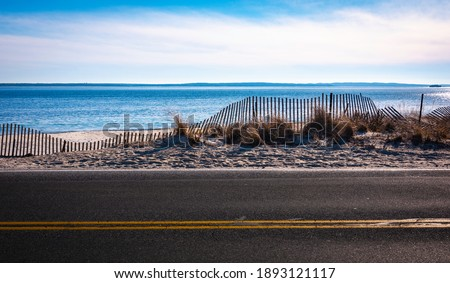Seascape with curved snow fence on the coastal road Royalty-Free Stock Photo #1893121117