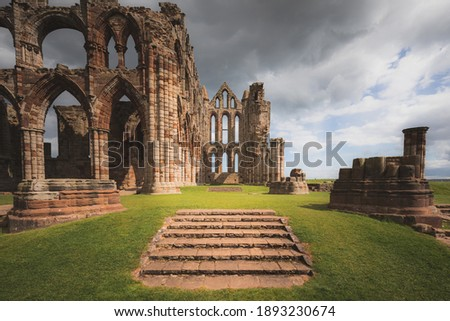 The historic landmark 7th century ruins of Whitby Abbey perched atop East Cliff north Yorkshire, England with a dark, moody sky. Royalty-Free Stock Photo #1893230674