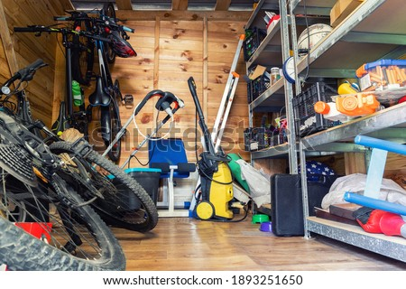 Suburban home wooden storage utility unit shed with miscellaneous stuff on shelves, bikes, exercise machine, ladder, garden tools and equipment. Messy and chaos at house yard barn. Organization order Royalty-Free Stock Photo #1893251650