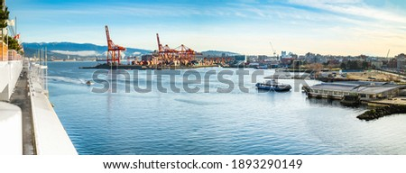 Vancouver Harbour panorama early mornings, on a sunny day. Waterfront city skyline with industry. A seabus ferry is leaving the waterfront station. Industrial cranes with cargo containers and tanker.  Royalty-Free Stock Photo #1893290149
