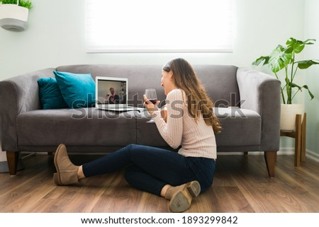 Good looking couple in a long-distance relationship is laughing and having a good time during a romatic online date  Royalty-Free Stock Photo #1893299842