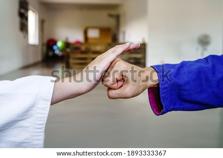 Close up on hand slap in brazilian jiu jitsu bjj or judo martial arts training - two female fighters bump fist before sparring Royalty-Free Stock Photo #1893333367