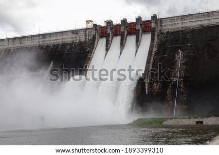 Water flowing over floodgates of a dam at Khun Dan Prakan Chon, Nakhon Nayok Province, Thailand  Royalty-Free Stock Photo #1893399310