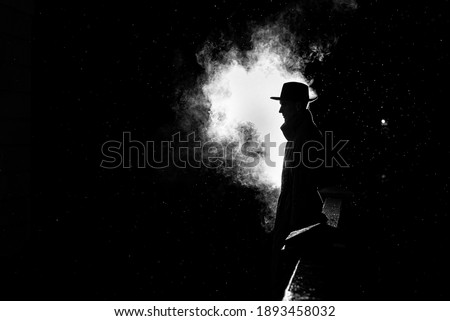 dramatic silhouette of a dangerous man in a hat at night in the rain in the city in the old crime  Royalty-Free Stock Photo #1893458032