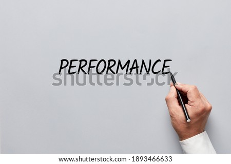 Male hand writing the word performance on gray background. Assessing job, work or business performance concept. Royalty-Free Stock Photo #1893466633