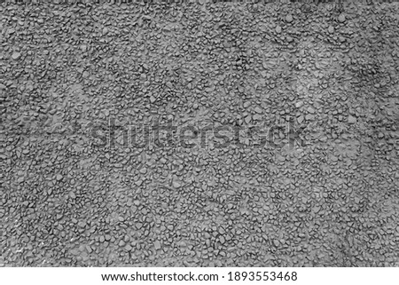 Texture of dark gray building facade cement plaster with fine gravel. Grey stone wall. Cheap finishing of facade of building with raw fine stone and plaster. Selective focus, noisy texture