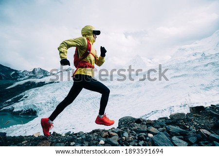 Woman trail runner cross country running up to winter snow mountain top Royalty-Free Stock Photo #1893591694