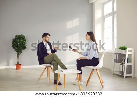Successful businessman or famous politician giving interview and sharing opinion with newspaper journalist. TV host with microphone asking young male celebrity questions in television talk show studio