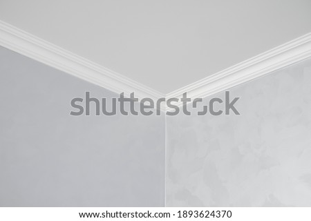 White ceiling with a white plinth in a room with gray painted walls. Decoration of the corner between the ceiling and the wall in the room. Ceiling molding in the interior. Detail of corner. Royalty-Free Stock Photo #1893624370