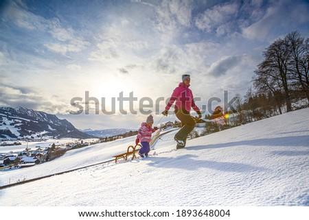Germany, Bavaria, Allgäu, Woman and daughter enjoying a winter day sledding