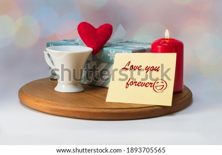 """Photo poster for Valentine's Day. A cup of coffee, a heart made of red cloth, a lighted candle, a gift box and a note with the inscription """"love you forever"""" on a light background with highlights."""