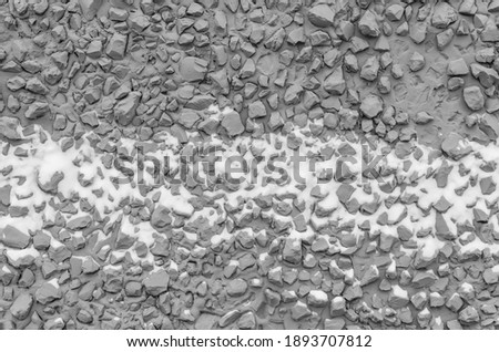 Texture of dark gray building facade cement plaster with fine gravel and stuck snow. Grey stone wall. Cheap finishing of facade of building with raw fine stone and plaster.