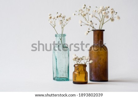 Three small glass handmade vases with white dried wild flowers. Brown and blue glass vintage bottles. Antique interior decoration objects.  Royalty-Free Stock Photo #1893802039
