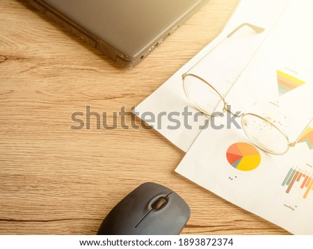 The Picture of Business Planning Concept.Economic analysis concept.Graph paper and glasses ,Mouse are placed on the wooden table.