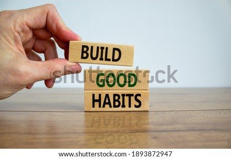 Build good habits symbol. Wooden blocks with words 'build good habits'. Male hand. Beautiful wooden table, white background, copy space. Business, psychological and build good habits concept. Royalty-Free Stock Photo #1893872947