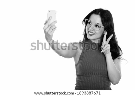 Studio shot of young happy Spanish woman smiling while taking selfie picture with mobile phone and giving peace sign