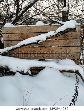 Wooden fence on the road in winter. Winter fence in the village. Winter outside the city. Wooden background