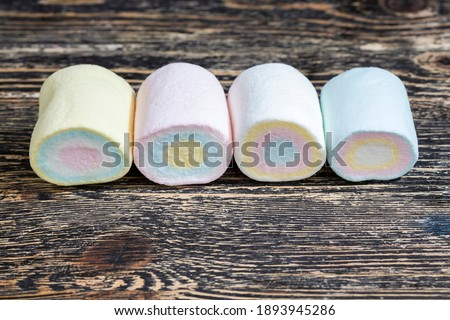 colored sweet soft cylindrical marshmallows made from sugar, gelatin, starch and other ingredients, closeup sweet marshmallows Royalty-Free Stock Photo #1893945286