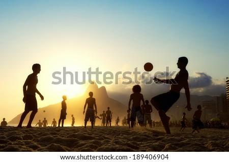 Sunset silhouettes playing altinho futebol beach football kick-ups soccer ball Ipanema Beach Rio de Janeiro Brazil