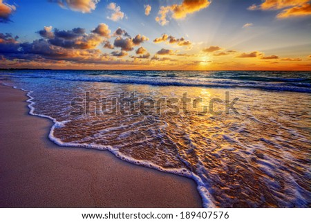 Colorful ocean beach sunrise with deep blue sky and sun rays #189407576