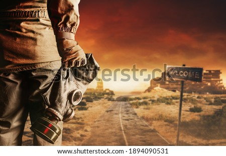 Photo of a stalker in jacket and gloves holding gas mask with filter on destructed apocalyptic wasteland city background. Royalty-Free Stock Photo #1894090531