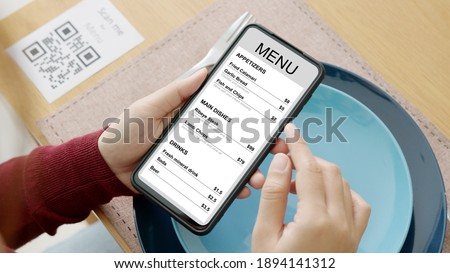 Hand's customer scan QR code for online menu service at table in restaurant during pandemic coronavirus. New normal contactless technology lifestyle protection coronavirus pandemic in restaurant Royalty-Free Stock Photo #1894141312
