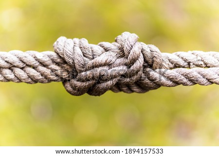 A selective focus of knotted ropes on blurred green background Royalty-Free Stock Photo #1894157533